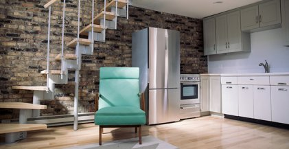 green armchair in front of staircase and kitchen with stainless steel appliances in Chicago studio apartment