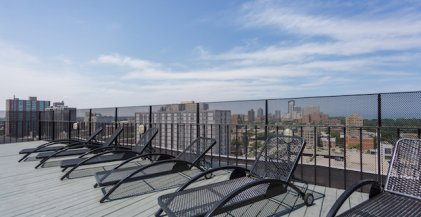 sundeck with black lounge chairs at Uptown apartment building The Covington Apartments