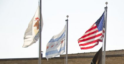 The Chicago flag flies beside the Illinois State flag and the American flag outside a business in Chicago, IL