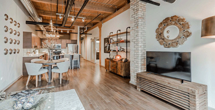 Modern loft with exposed wood ceiling, exposed ductwork, and open kitchen with industrial lighting