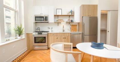 kitchen of Chicago Loop apartment for rent with natural wood finished cabinets, white counters and stainless steel appliances