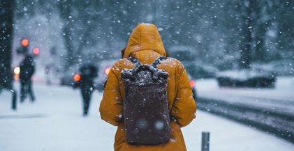 person wearing yellow parka and backpack on snowy city street