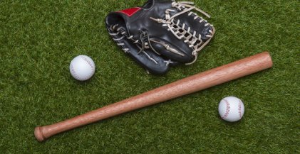 baseballs and baseball bat lying on grass beside black leather baseball mitt
