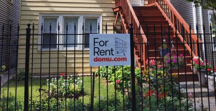 a Domu for rent sign on a wrought iron fence in front of a Chicago apartment for rent