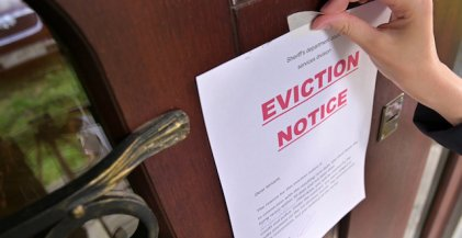 hand taping an eviction notice to a door