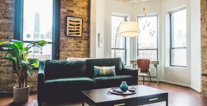 a green sofa with an exposed brick wall behind it in the living room of a Chicago apartment for rent