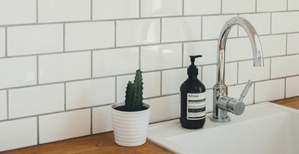 stainless steel faucet and white backsplash in apartment kitchen