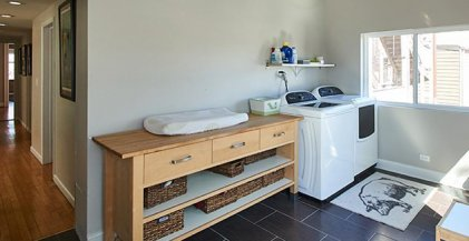 a sunny laundry room with washing machine and dryer side-by-side in a Chicago apartment for rent