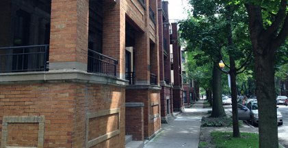 brick chicago apartment building on tree lined neighborhood street in Chicago IL