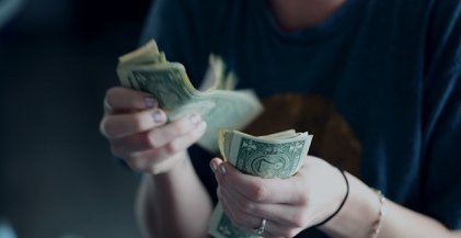 woman in a blue t-shirt counting money