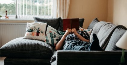 person lying on couch reading a book in an apartment while furloughed from their job