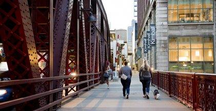 pedestrians walking across Chicago River on bridge in River North neighborhood