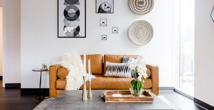 a tan leather sofa in a living room with concrete coffee table in one bedroom apartment for rent in Fulton Market District, Chicago IL