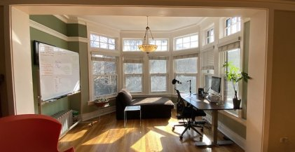 apartment home office with adjustable standing desk and whiteboard in front of windows