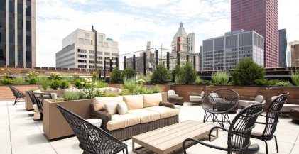 green planter boxes with shrubs next to lounge furniture on rooftop deck of downtown Chicago apartment building