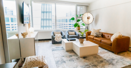 living room with grey area rug and white coffee table in front of brown leather sofa in a Chicago apartment
