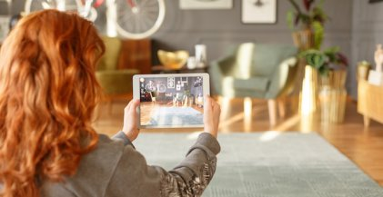 woman holding tablet while taking photo of apartment interior