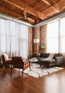 loft apartment with exposed brick walls and timber ceilings