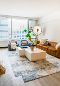 living room of Chicago apartment for rent with tan leather sofa and white coffee table in front of large windows