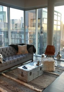 a corner view of downtown Chicago through floor-to-ceiling glass windows in a luxury apartment for rent in Chicago