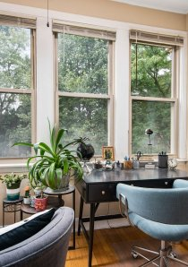 a home office with windows and low bookcases in the sunroom of a Chicago apartment