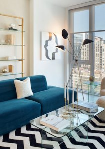 blue sofa and black and white striped rug in living room of new Chicago apartment