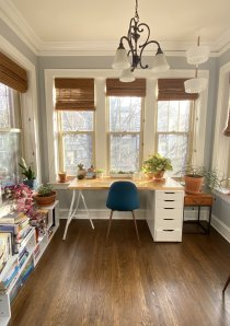 sun room of Chicago apartment converted into home office space with desk and task chair