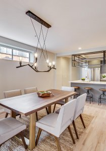 dining room with wooden dining table and grey chairs underneath contemporary chandelier light in Chicago apartment for rent