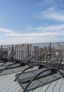 sundeck with black lounge chairs on top of an apartment building in Uptown, Chicago