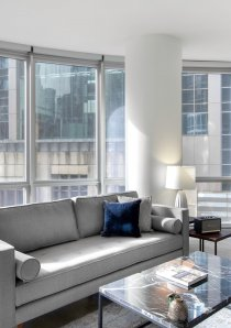 grey sofa and black marble coffee table in living room of a Chicago apartment for rent