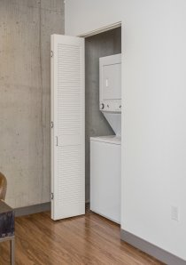 a Chicago apartment with exposed concrete wall and small desk opposite a closet containing laundry machine