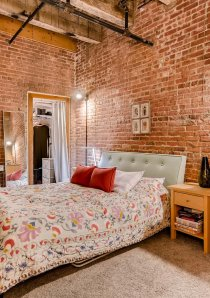 bedroom with exposed brick walls and timber ceilings in Chicago loft apartment