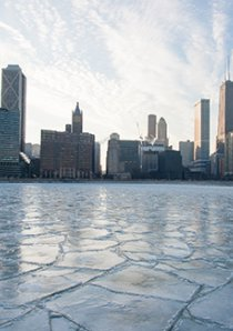 a frozen layer of ice covers Lake Michigan near apartment buildings in downtown Chicago