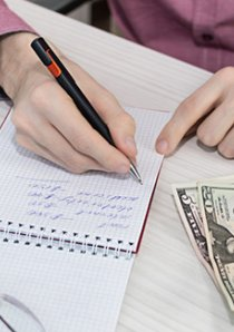 person writing in a steno notebook and calculating security deposit payments for their Chicago apartment