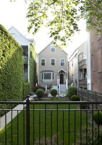a workers cottage in Chicago's Bucktown neighborhood with a large front yard behind a black iron fence
