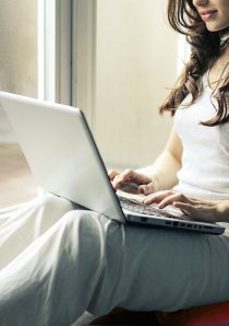 woman in grey tanktop using a silver laptop computer
