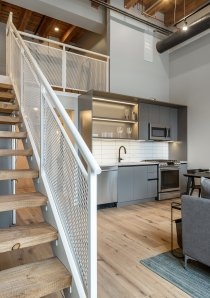 a 1 bedroom loft apartment with stainless steel kitchen appliances in background and a staircase with white metal railing leading in foreground