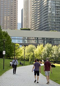 people walking in a park beside new apartments in Lakeshore East neighborhood of Chicago