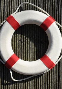 a white and red lifesaver ring hanging on a corrugated metal wall