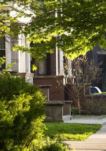 man wearing a backpack walks on sidewalk in front of Chicago apartment buildings in Logan Square