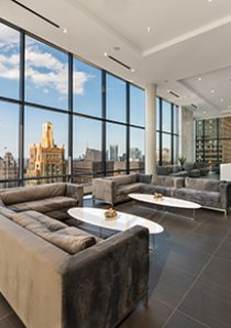a resident lounge in a luxury apartment building with floor-to-ceiling glass windows looking at Michigan Ave in Chicago
