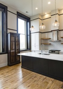 custom designed kitchen with large kitchen island underneath hanging pendant lamps in Chicago loft apartment for rent