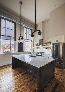 custom kitchen with oversized kitchen island and marble counters in loft apartment for rent in Chicago
