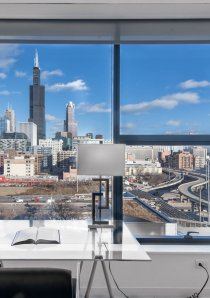 a desk in a Chicago apartment with a view of downtown Chicago skyline
