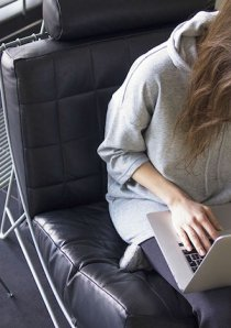 apartment renter using a silver laptop while sitting on a black leather chair