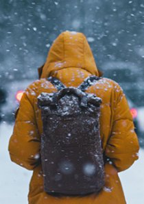 a person wearing a yellow parka and backpack stands on the sidewalk during a snowstorm