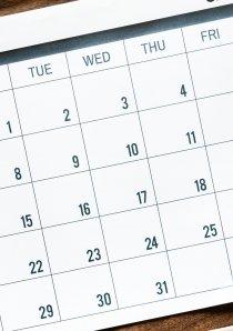 a desk calendar next to an alarm clock on a wooden desk surface