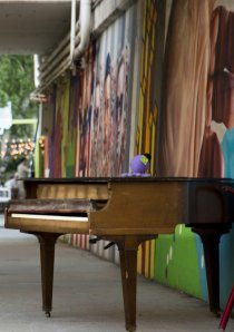 a piano next to a mural painted along a viaduct in the Rogers Park neighborhood of Chicago