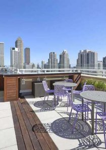 outdoor dining setups on rooftop of Chicago apartment building with views of the city skyline in background