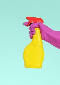 a person wearing pink rubber glove holds a yellow bottle of disinfectant spray